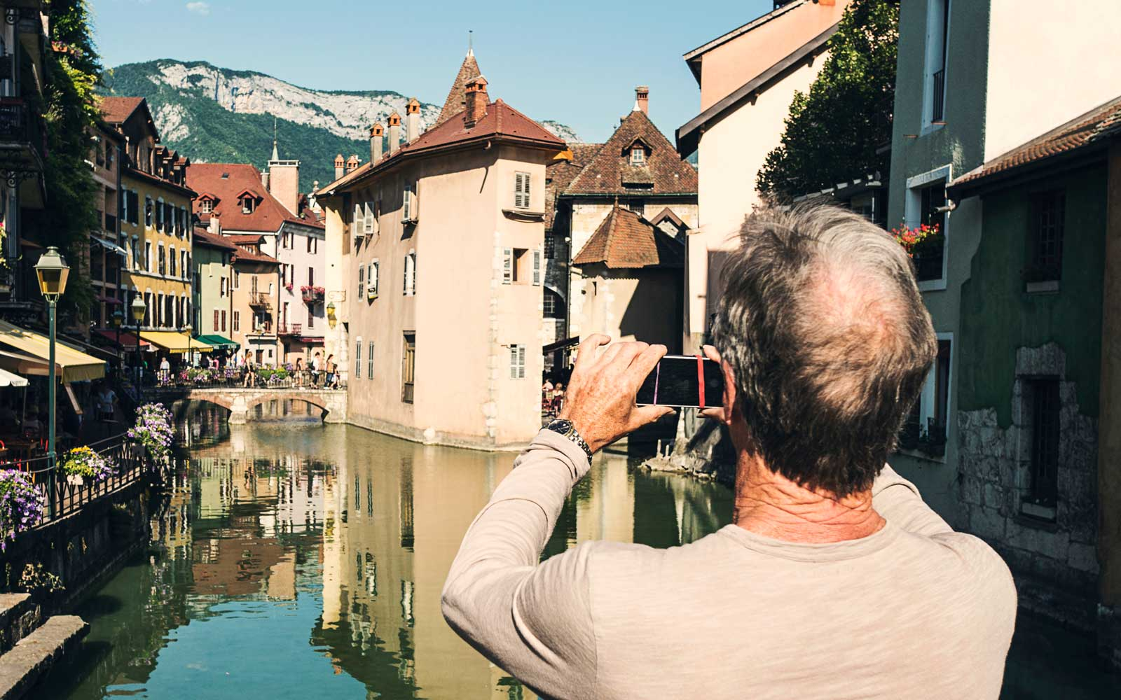 Senior Man taking photo on Smart Phone in Annecy, France