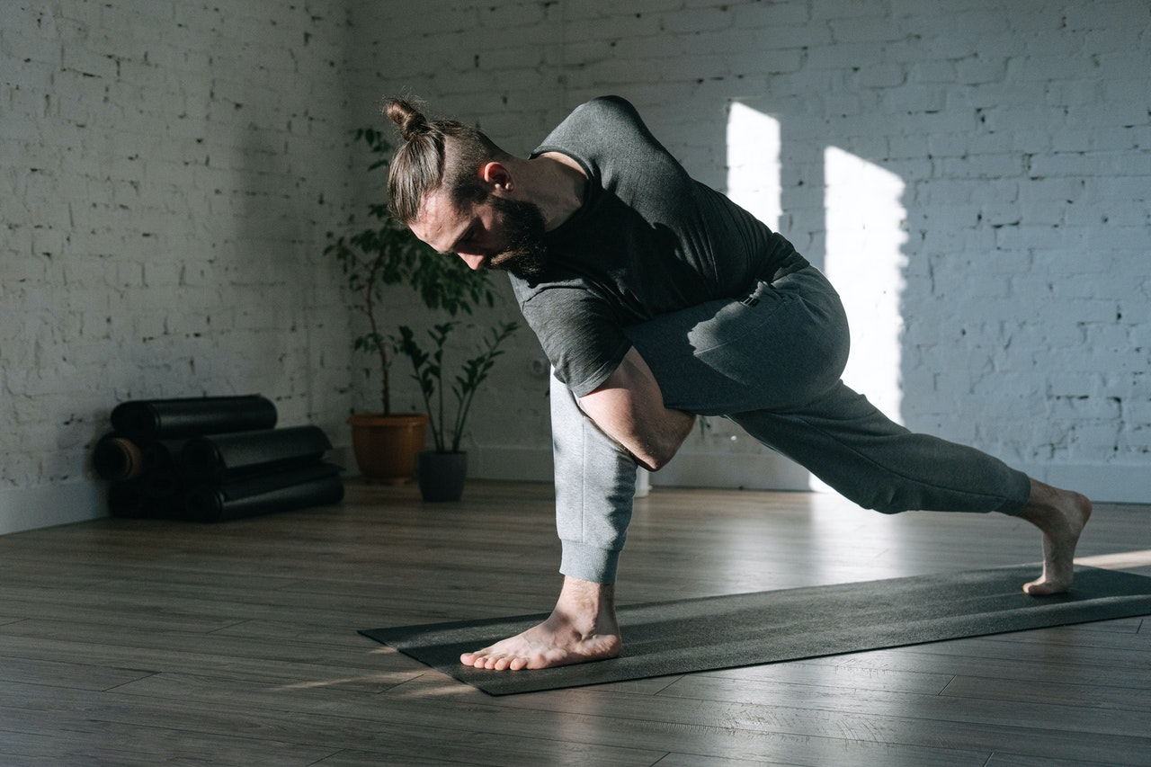 man stretches with yoga
